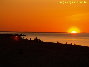 Beachgoers catch the last of the sun's rays on a late summer evening.